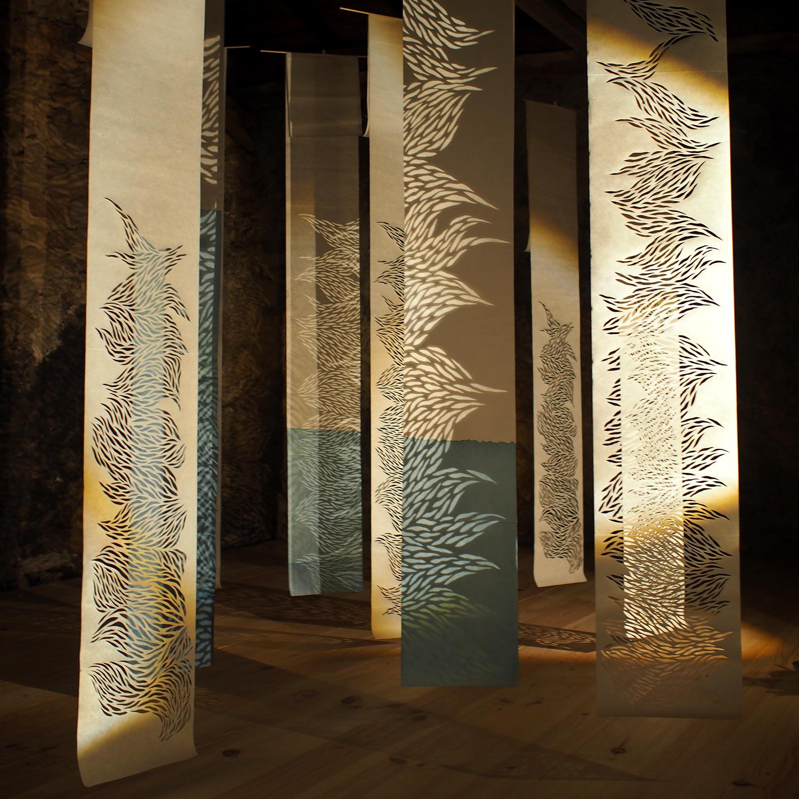 installation théâtre d'ombre faite de kakémonos de papier washi blanc teints en bleus ou incisés suspendus