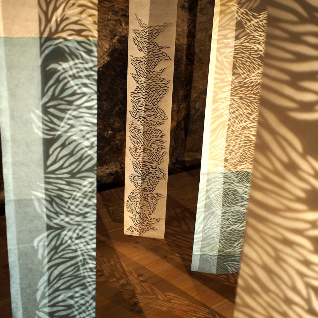 Jeu de lumière, projection d'ombre à travers des kakémonos de papier découpés