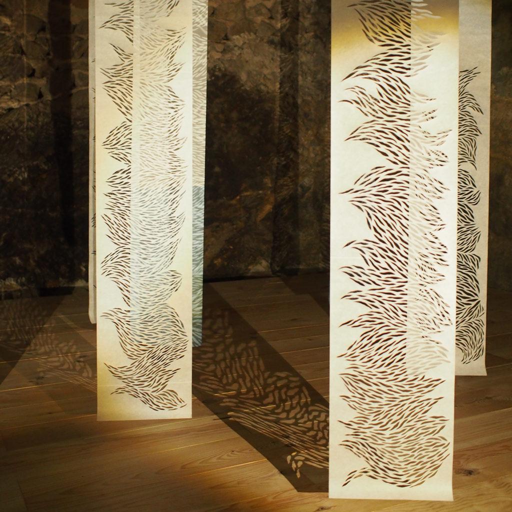 Kakémonos de papier découpé projetant des ombres au sol