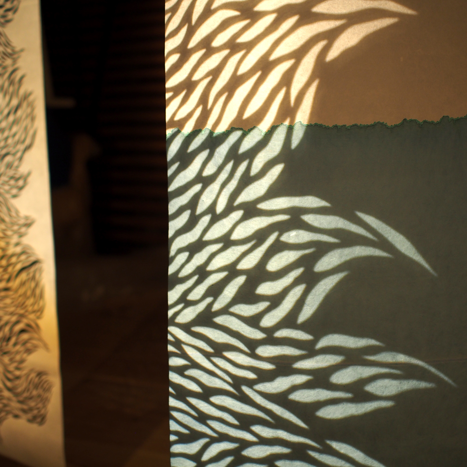 motif organique en lumière projeté sur papier washi teint en bleu
