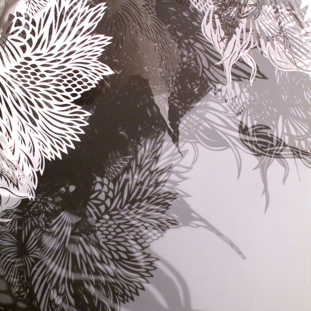 Détail du motif découpé et ombres projetées plus ou moins sombres sur le mur