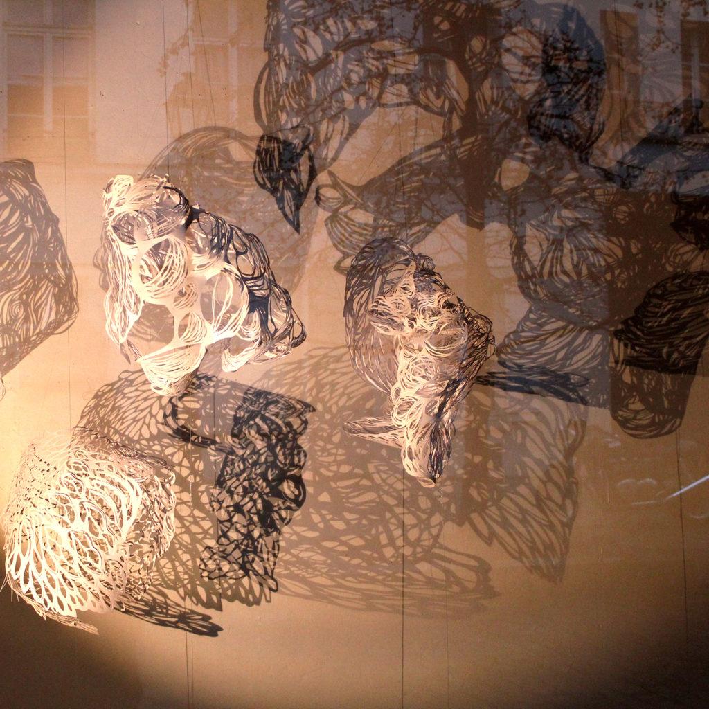 """Mobiles """"nuages"""" en papier découpé blancs et leur ombre projetée sur un mur"""