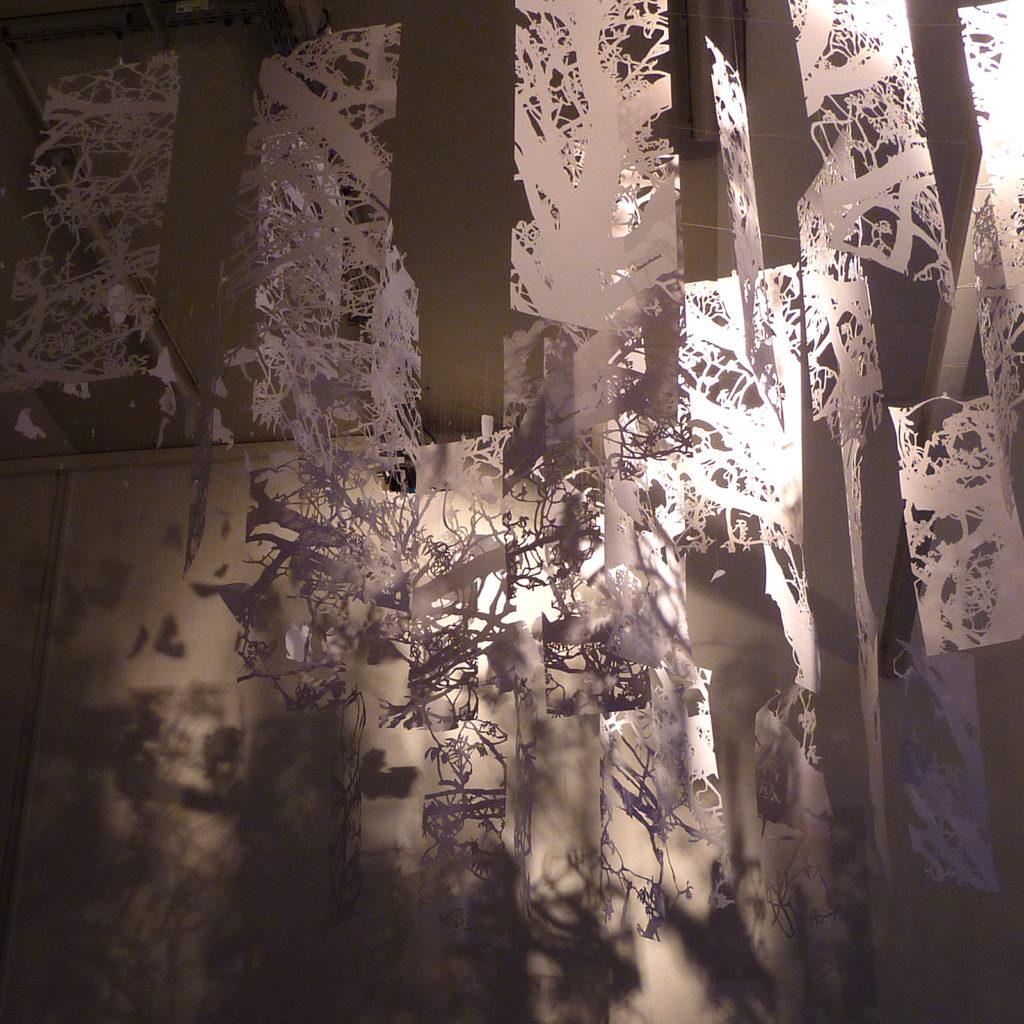 Installation en papier découpé blanc composée de trente deux kakémonos représentant un chêne