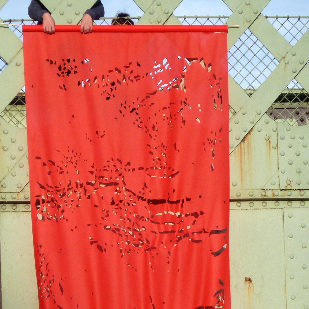 Gros plan de l'accrochage d'un des kakémonos au maillage du pont