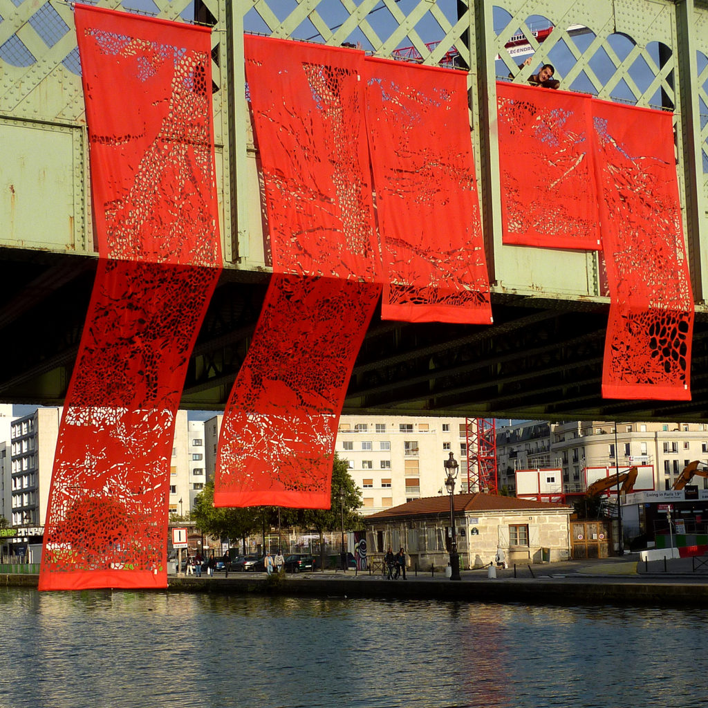 Installation géante composée de 5 kakémonos de papier découpé suspendus sur le pont de l'Ourcq
