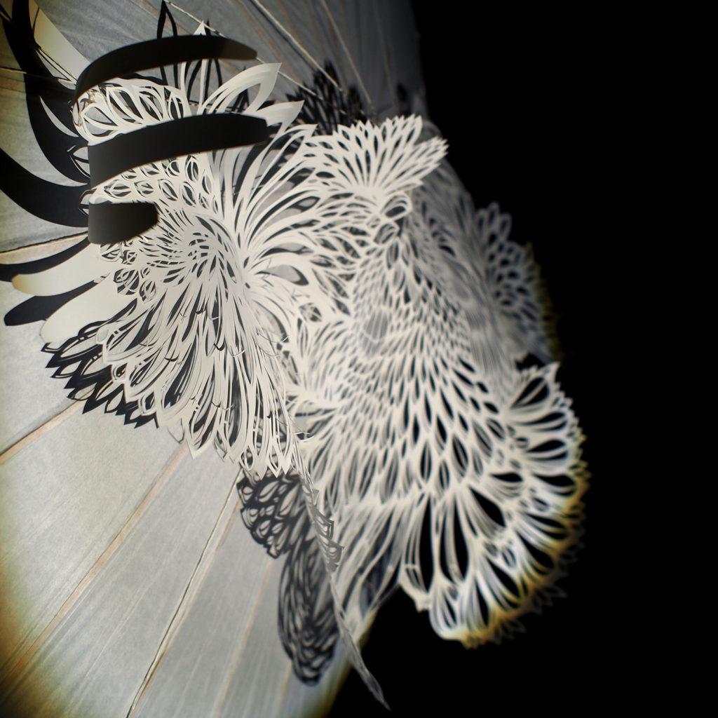 Papier découpé blanc motif plume appliqué sur ombrelle en papier