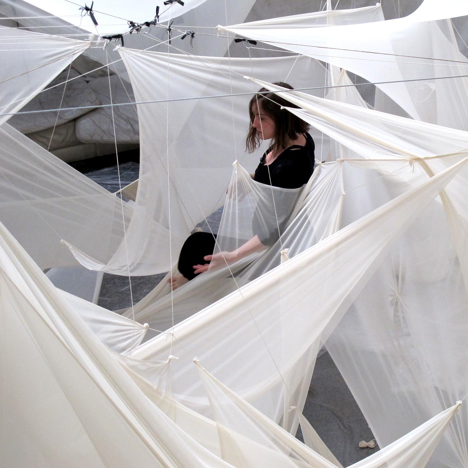 Fragments d'une danseuse entre les voiles blanches de linstallation